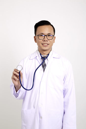 Portrait of smiling doctor holding stethoscope while standing against white background