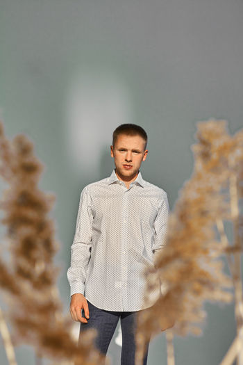 Young man looking away while standing against wall