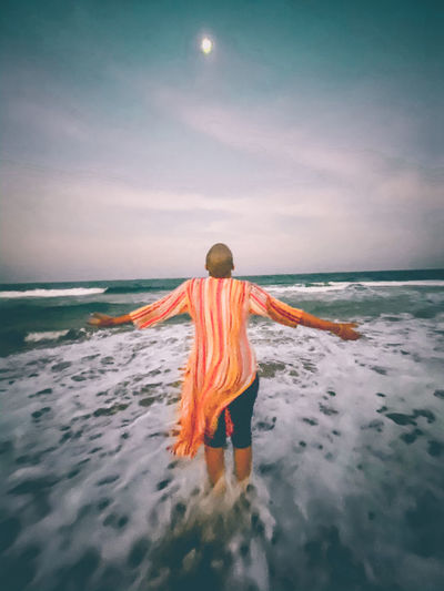 Rear view of woman on beach against sky
