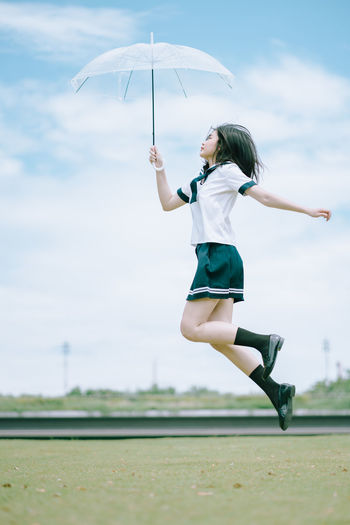 Side view of young woman with umbrella jumping in park
