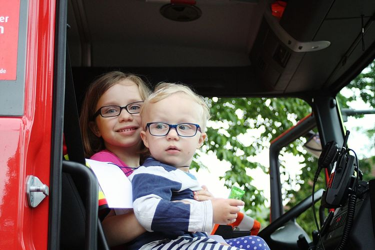 Portrait of siblings sitting in fire engine