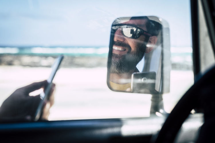 Portrait of man using smart phone in car