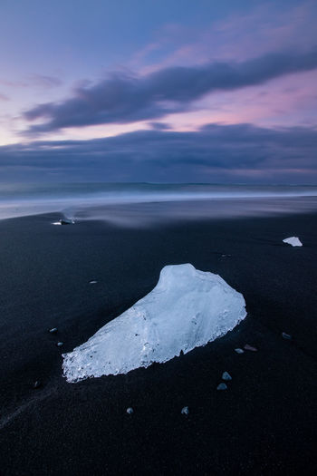 Ice chunk on black sand beach at dawn in Diamond beach, Jökulsarlon, Iceland Beauty In Nature Travel Destinations Golden Hour Iceland Nordic Countries Diamond Black Sand Ice Ice Chunks Chunk Water Sea Beach Wave Astronomy Sand Cold Temperature Sunset Ice Tide Coast Coastline Ocean Lagoon Glacier