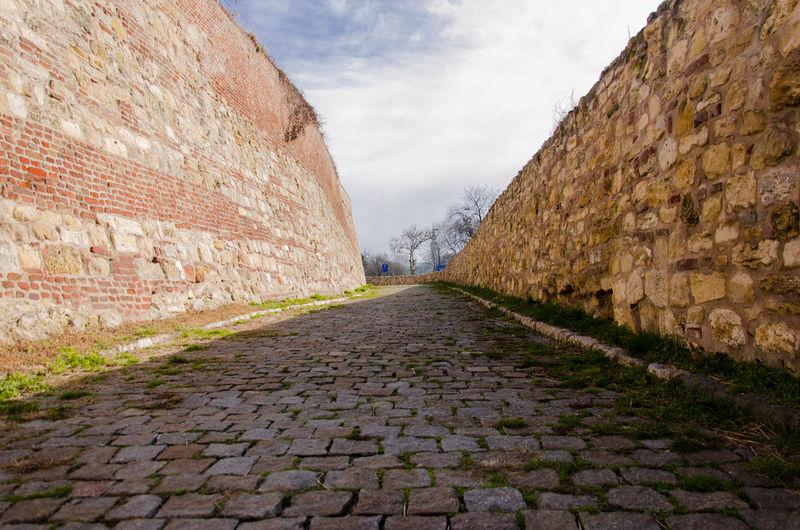 Footpath amidst wall against sky