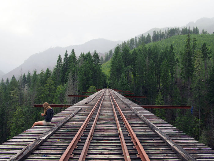 Side view of woman sitting on vance creek viaduct leading towards mountains