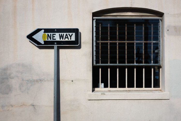 One Way Sign By Window Against Building