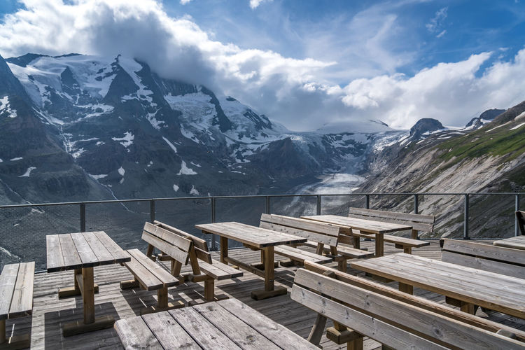 Empty benches on snowcapped mountains against sky