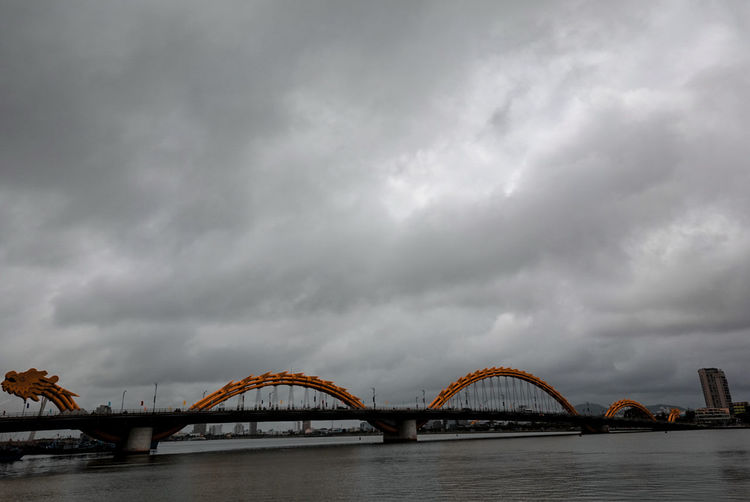 Low angle view of bridge over river against cloudy sky