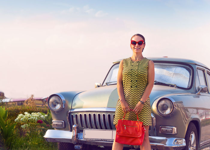 Portrait of young woman standing on car against sky