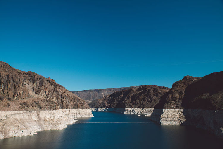 Colorado river amidst mountain at hoover dam against clear blue sky