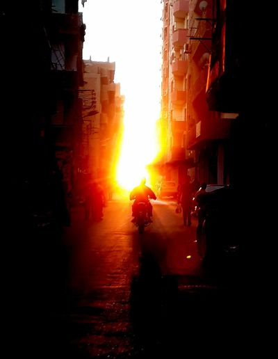 Driving to the hell gate..a man ride a motorbike in the street in the sunset in uperegypt Flame Burning Real People Sunset City People Day Architecture Photooftheday Illuminated Mobilephotography Streetphotography Nature Red Lifestyles Sky Uper Egypt