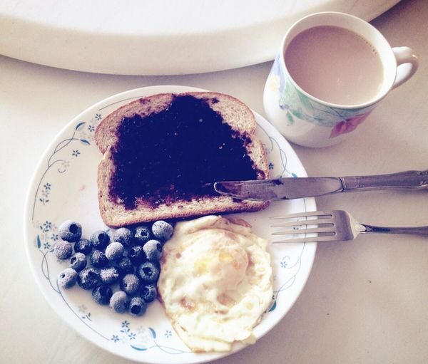 High angle view of blueberry with bread jam and fried egg by tea on table