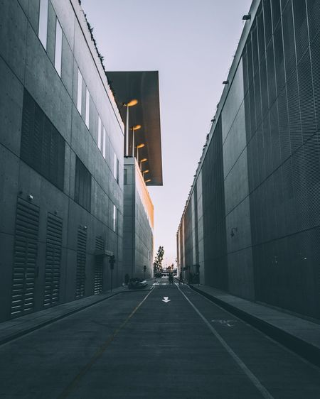 Road amidst buildings against clear sky