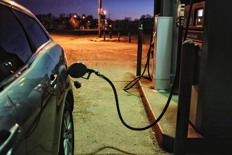 Car refueling in gas station at night