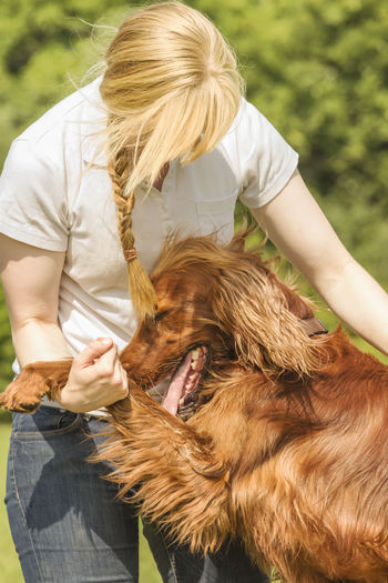 Dog trainer cuddling with irish setter Love Affection Animal Themes Animal Training Blond Hair Day Dog Dog Trainer Domestic Animals Irish Setter Leisure Activity Lifestyles Long Hair Mammal Nature One Animal One Person Outdoors Pets Real People Sympathy Young Adult Young Women