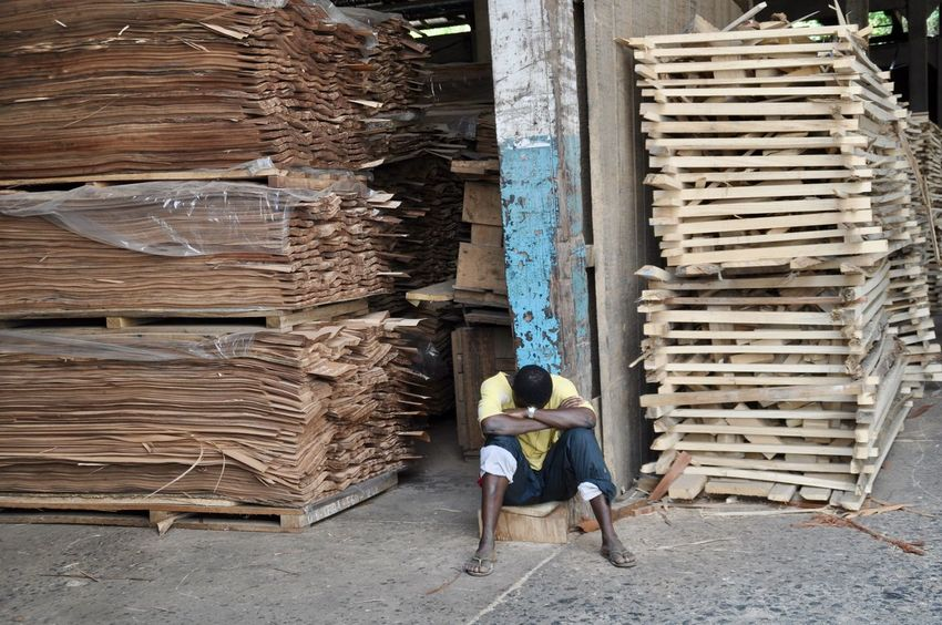 Taking a rest. African Ghana Wood Working Adult Africa Carving Full Length Industry Large Group Of Objects One Man Only One Person Pallet Pause Pausing Pile Rest Stack Taking A Rest  Tired Warehouse Wood - Material Woodcut Working