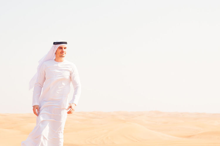 Man in traditional clothing standing on sand dune against sky