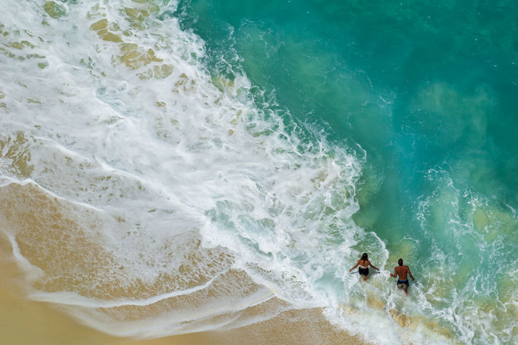 BALI, INDONESIA - 3rd FEB 2019; Aerial view of people swimming in the transparent turquoise sea over sunny day at Kelingking beach. Top view from cliff. Sea Water Motion Beach Wave Two People Surfing Sport Land Aquatic Sport Men High Angle View Nature Lifestyles People Day Beauty In Nature Togetherness Leisure Activity Outdoors Power In Nature Bali INDONESIA Surf Love