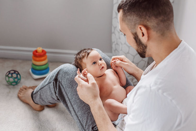Man playing with baby girl at home