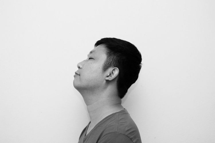 Side view of man with eyes closed against white background