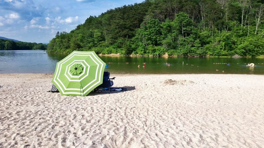 Green umbrella on sand beach in summer Day Outdoors Nature Sky Umbrella People In The Distance People In The Water Summer Travel Destinations Lake Habeeb Swimming Sunning Shade Refreshment Sand Sand Beach The EyeEm Collection The Photojournalist - 2017 EyeEm Awards Sommergefühle 100 Days Of Summer The Premium Collection