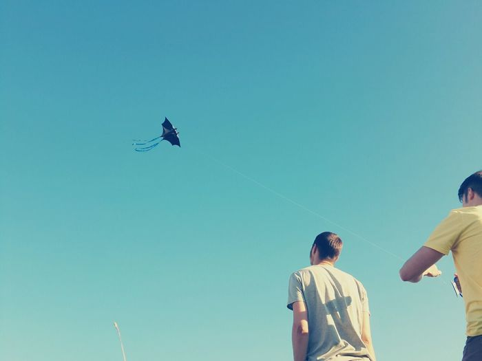 Low angle view of friends flying kite against clear blue sky