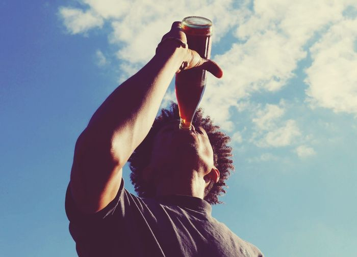 Low angle view of man drinking cola against sky