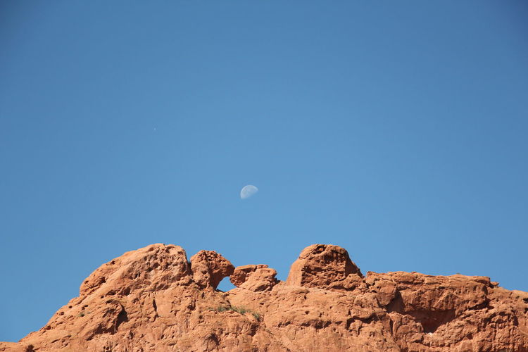 Kissing Camels Astronomy Beauty In Nature Blue Clear Sky Day Garden Of The Gods Low Angle View Moon Nature No People Outdoors Physical Geography Scenics Sky Tranquil Scene Tranquility