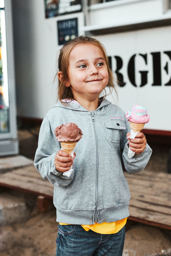 Happy smiling little girl holding two ice cream standing in front of food truck