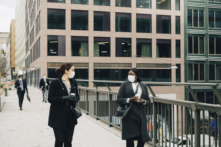 Man and woman walking on building in city