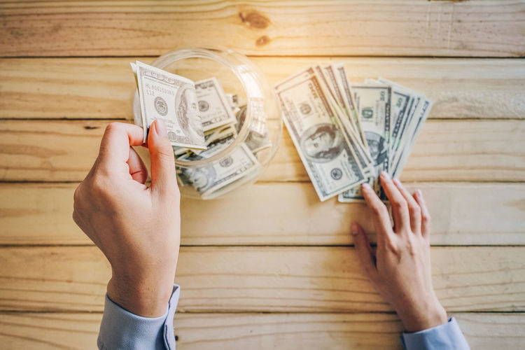 Allocate funds for the future. Holding Hands Jidpipat_Photo Adult Banknote Body Part Business Currency Directly Above Finance Hand Holding Human Body Part Human Foot Human Hand Indoors  Lifestyles Low Section Money One Person Paper Currency Real People Savings Wealth Women Wood - Material