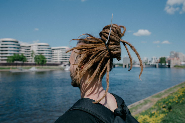 Close-up of man with dreadlocks standing by river in city