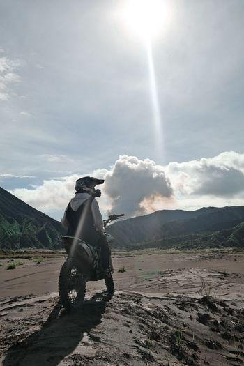 Man standing on mountain road against sky