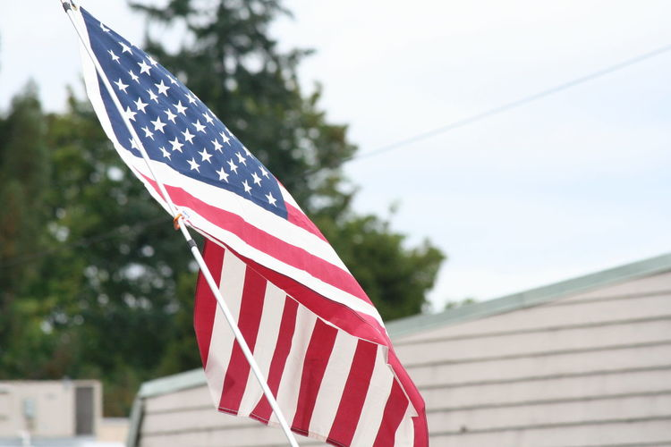American flag against sky on fourth of july parade