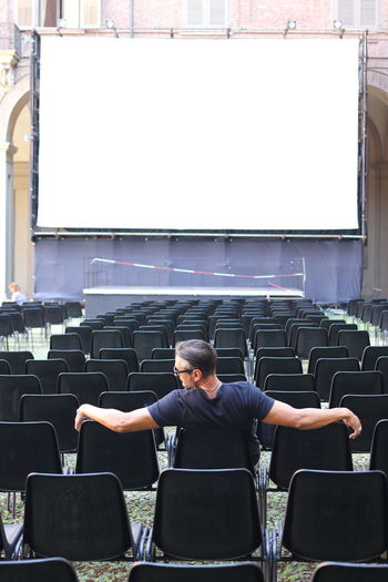 Rear view of man sitting against projection screen on chair