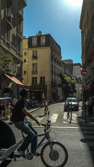 Paris - August 2016 Caught In The Moment Europe France Paris Woman People Watching Bicycle Architecture Cycling Transportation City Riding Street Mode Of Transport Road Sunlight Day Land Vehicle Real People Built Structure Men Motorcycle Lifestyles Building Exterior People Outdoors