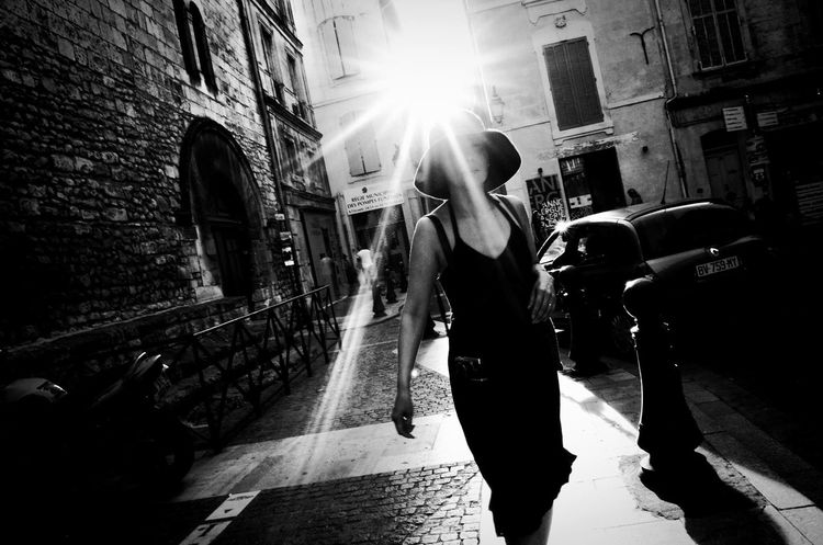 Summertime Sun Flare Dress Hat Woman With Hat Streetphotography Hight Contrast BW_photography 28mm Ricoh Gr Against The Light Architecture Lens Flare Street One Person People Day