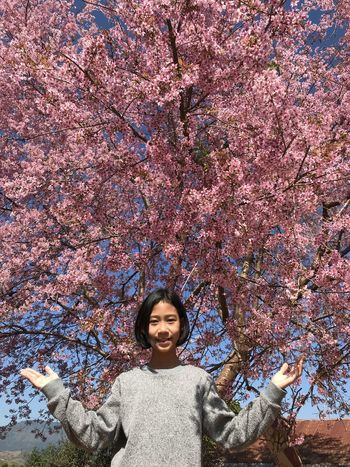 Beauty In Nature Casual Clothing Change Cherry Blossom Cherry Tree Day Flower Flowering Plant Front View Growth Happiness Leisure Activity Lifestyles Looking At Camera Nature One Person Outdoors Plant Portrait Smiling Springtime Standing Tree Young Adult Young Women