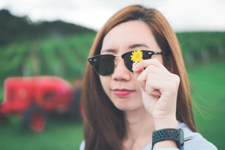 Close-Up Portrait Of Young Woman In Sunglasses Holding Yellow Flower