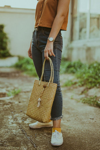 Low Section Of Woman Holding Wicker Bag While Standing Outdoors