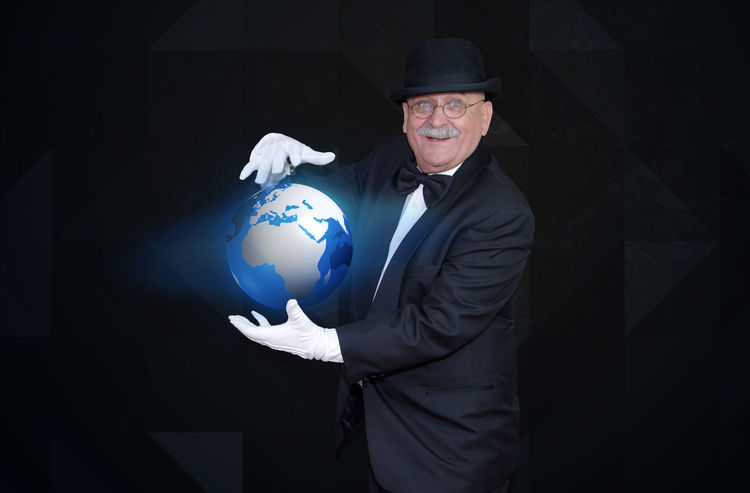 Man magician enhancing tiny planet, future performance tecnology concept Earth Eco Power Wizard Businessman Communication Ecology Element Future Futuristic Globe Holding Holding On Magician Nice One Person Smiling Sorcerer Trick  Water