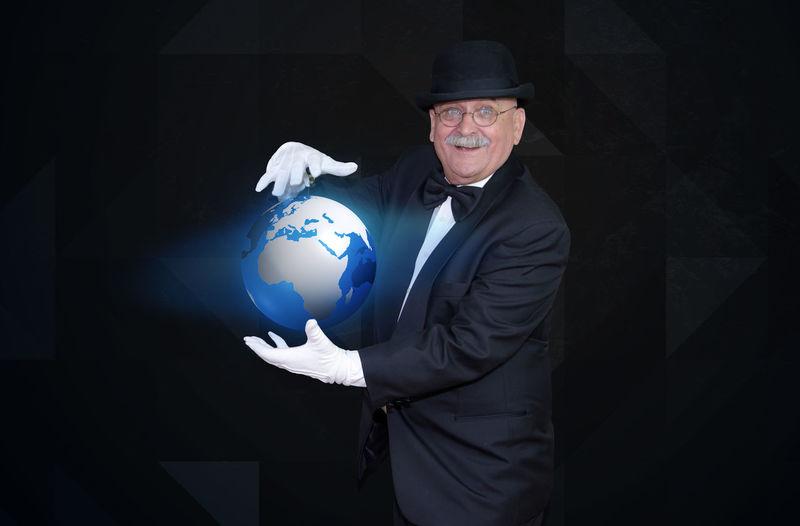 Portrait Of Senior Man Holding Illuminated Globe