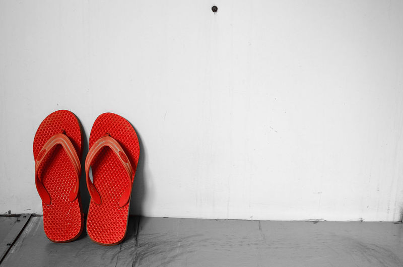 Pair Of Red Slippers Leaning Against Wall