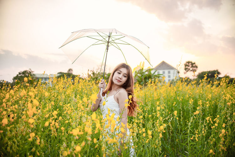 Portrait of beautiful woman standing on field against sky