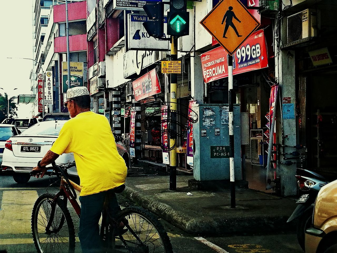 REAR VIEW OF MAN WITH BICYCLE ON ROAD