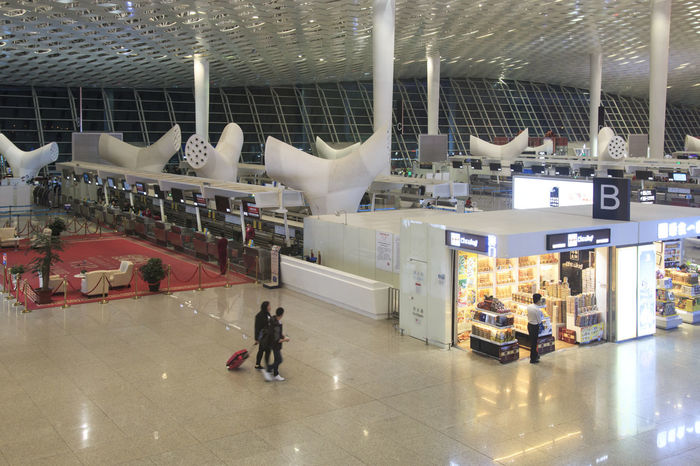 Shenzhen, China - January 5, 2016: People walking inside the Shenzhen Bao'an International Airport in Guandong, China Airplane Airport Bao'an International Airport Canton Casual Clothing China City City Life Day Guandong City Illuminated Leisure Activity Lifestyles Modern Tourists Travel Trolley Yunnan