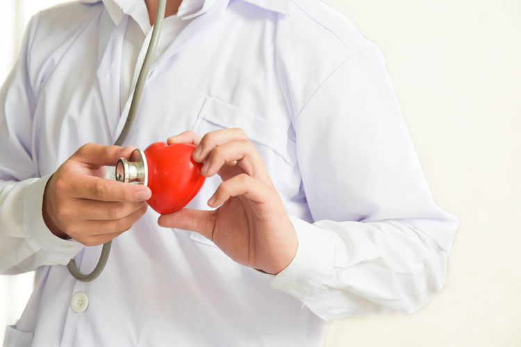 A doctor with stethoscope examining red heart healthcare and medical concept Aid Care Doctor  Emergency Healthcare Hospital Man Red Surgeon Uniform Cardio Cardiology Clinic Doctor  Hand Health Healthcare And Medicine Heart Heart Shape Insurance Medical Physician Specialist Stethoscope  Treatment