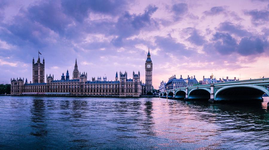 Westminster bridge over thames river against big ben against cloudy sky
