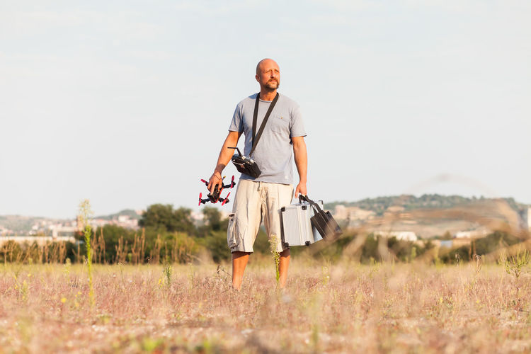 Mid adult man with drone standing on grassy field against clear sky