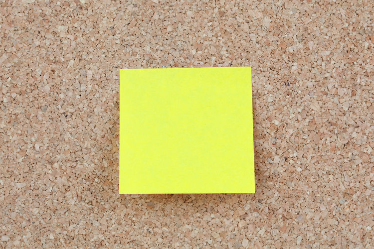 Close-up of yellow blank adhesive note on bulletin board
